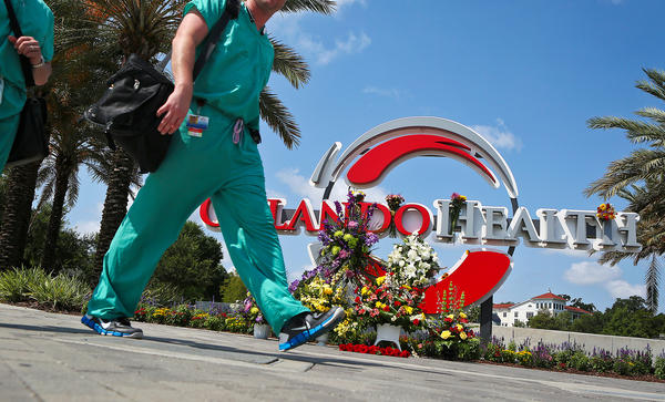 Medical professionals walk by a makeshift memorial set up at the Orlando Health sign in June in Orlando, Fla.