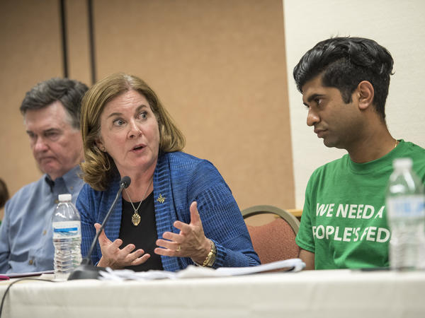 Esther George (center), president of the Kansas City Federal Reserve Bank, speaks as Shawn Sebastian (right), field director of the Fed Up coalition, listens Thursday during a meeting on the sidelines of an economic symposium in the Jackson Hole, Wyo.