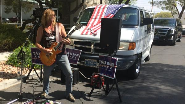 "Steven Boz performs outside of a Trump campaign office. He says he loves Trump's ""attitude."""