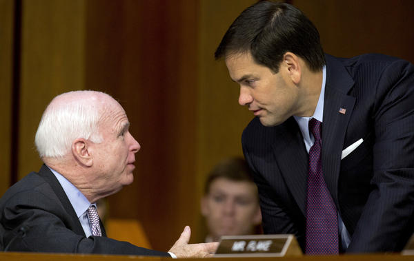 Sen. John McCain, R-Ariz., and Sen. Marco Rubio, R-Fla., talk on Capitol Hill in 2014. Both are expected to win their primaries for re-election Tuesday.