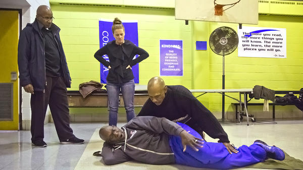 Neighbors learn how to move gunshot victims safely. Temple emergency department nurse Oscar Hankinson, Jr., acts as the victim, while emergency department nurse Kayne Puchon looks on.