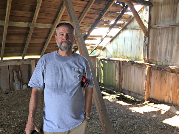 Mike Hudson, standing in the hayloft of his current barn project, says he will deconstruct about 10 to 12 barns in the next year. He sells the reclaimed wood at his lumberyard in Elbert, Colo.