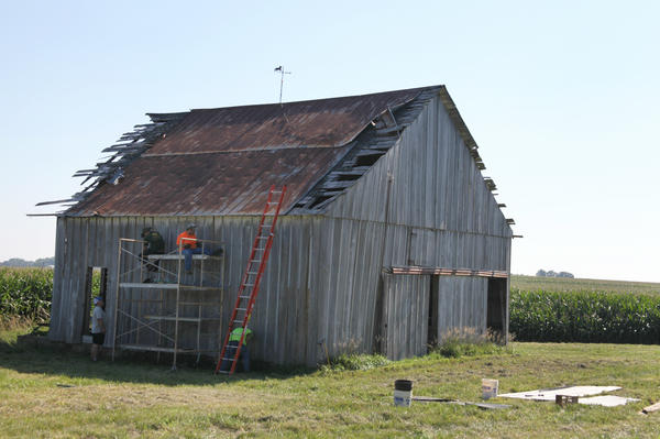 Mike Hudson's team starts pulling apart an old barn on the shady side because the temperature is approaching 90 degrees in Malta Bend, Mo. The pieces of the barn will be sold as reclaimed barn wood.