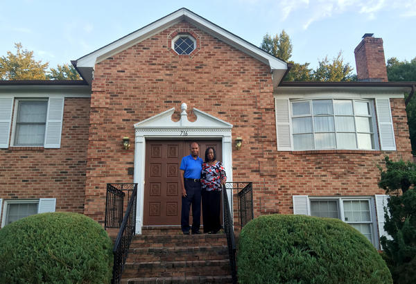 "Grattan (left) and Evelyn Betancourt stand in front of their home in Fort Washington, Md., in one of the wealthiest majority-black counties in the United States: Prince George's, just east of Washington, D.C. But the reality, Grattan says, is ""that many people here, even though they've lived here for many years, are fighting to save their homes"" — the Betancourts among them."