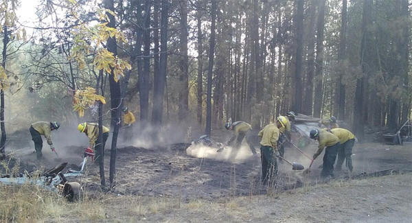 Firefighters mop up remaining fire and heat near residences threatened by the Cayuse Mountain Fire.