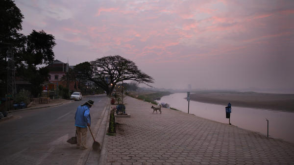 A municipal worker sweeps along a pathway near the Mekong river, in the capital Vientiane, Laos.
