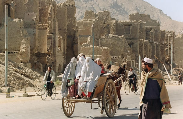 Past the ruins of Kabul's former commercial district, three women ride on the back of a donkey cart in November 1996, two months after the Taliban took control of the war-ravaged city.