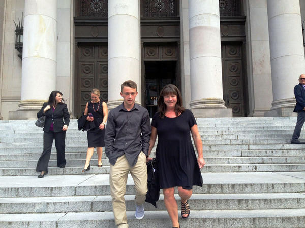 Carter McCleary, 17, and his mother Stephanie leave the Washington Supreme Court following a hearing in the nearly decade-old school funding lawsuit that bears their name.