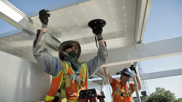 Workers install solar panels on the roof of the Bullitt Center in Seattle.