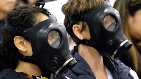 Protesters wear gas masks at a hearing over a leak at the Southern California Gas Co.'s Aliso Canyon Storage Facility near the Porter Ranch section of Los Angeles. On Tuesday, the utility pleaded no contest to a misdemeanor and agreed to pay $4 million to settle the case.