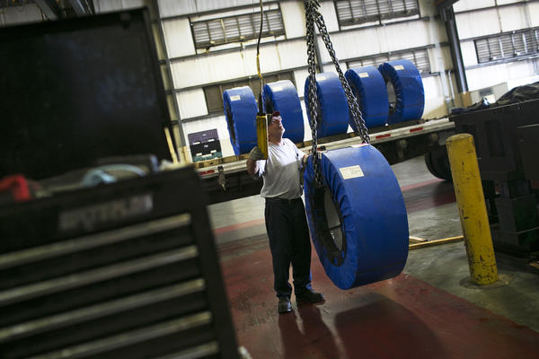 Darren Holly steers coils of steel through Pentaflex, a manufacturer of parts for heavy trucks, in Springfield, Ohio.
