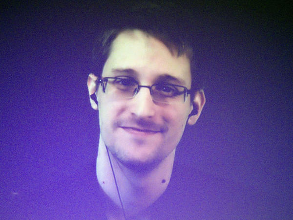 "Edward Snowden, who is in Moscow, is seen on a giant screen during a live video conference for an interview as part of Amnesty International event in Paris in December 2014. The House Permanent Select Committee on Intelligence published a summary report accusing Snowden of causing ""tremendous damage to U.S. national security."""
