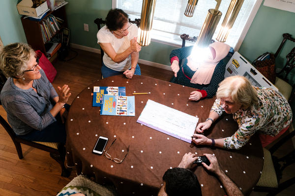 Beverly Leach (right) leads an ESL course for Ghada and her husband Osama, two newly resettled refugees from Syria, in their home. They are accompanied by other volunteers.
