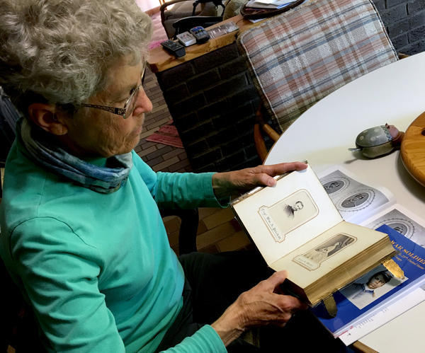 Aneita Atwood Gates looks through an album of her great-grandmother's side of the family, which includes a picture of her great-grandfather William A. Prickitt, seen here.
