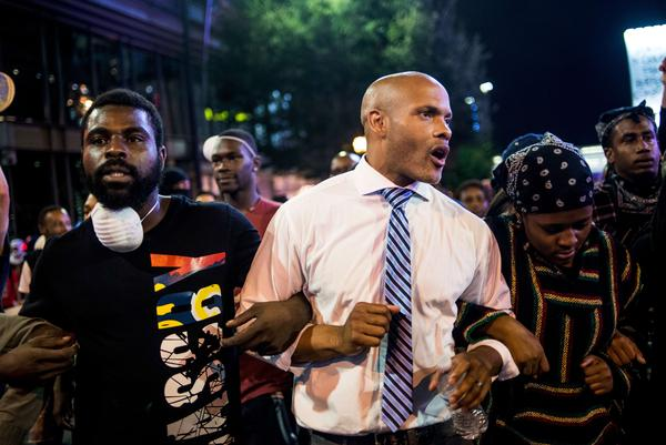 Protesters, including public defender Toussaint Romain (center), march in the early hours of Friday in Charlotte, N.C. Despite a midnight curfew, police allowed the peaceful march to continue without interference. Protests began on Tuesday night following the fatal shooting of 43-year-old Keith Lamont Scott.