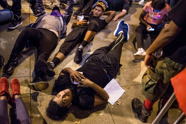 Demonstrators lie on the ground as they protest in front of the police station Thursday night in Charlotte, N.C. After two nights of violent unrest, protests on Thursday night were mostly peaceful, with no injuries or arrests reported.