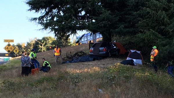 Officials inspect the scene at the Seattle homeless camp along Interstate 5 where a car ran off the road and resulted in the death of a young man who was in his tent.
