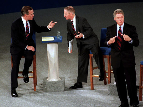 President George Bush, left, talks with independent candidate Ross Perot as Democratic candidate Bill Clinton stands aside at the end of their second presidential debate in Richmond, Va., on Oct. 15, 1992.