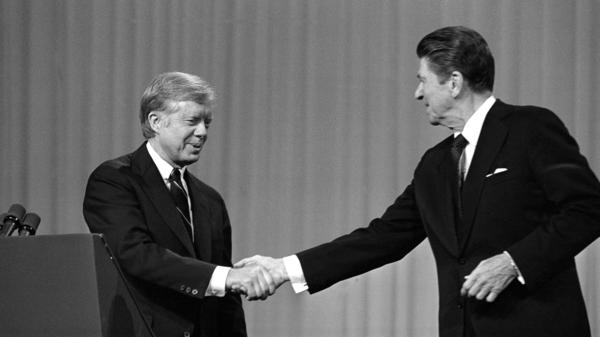 President Jimmy Carter, left, and Republican presidential candidate Ronald Reagan shake hands after debating in the Cleveland Music Hall on Oct. 28, 1980.