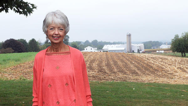 Terri Roberts at her home in Strasburg, Pa., a neighboring Amish farm in the distance behind her.