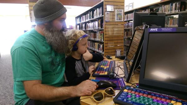 Eric Sebastian and his son Bob play a computer game at the library in Roseburg.