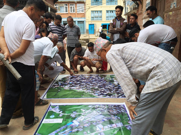 Residents of Panga, a town in Nepal hit hard by the 2015 earthquake, study a map of their area put together with drone images that Meier and his partners gathered.