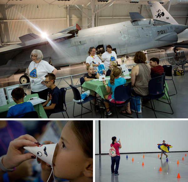 "Sean Mclaughlin (top, center) sits with a friend as they pick out their pilot code names. Audrey Strauss, 8 (bottom, left), tries on her decorative ""nose cone"", inspired by the nose cone of a plane. Nathan Ferraro, 10 (bottom, right), plays the role of a plane during a marshaling activity as his mom, Cora, takes a photo."