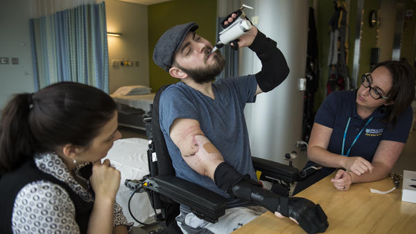 Fiancee Jessica Paker looks on as Ret. Marine Sgt. John Peck works with occupational therapist Meredith Grinnell. Peck, who was injured in Afghanistan in 2010, recently received a double arm transplant after a two-year wait on a transplant list.