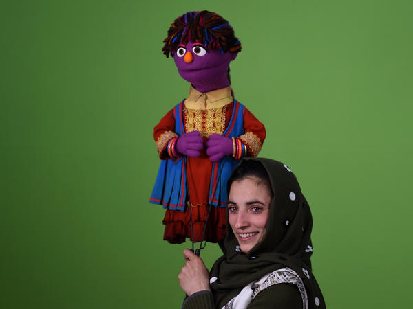With purple skin and an orange nose, her multi-colored braids wrapped in a headscarf, Zari is Sesame Street's first female Afghan Muppet. Held by Afghan puppeteer Seema Sultani, Zari helps promote education for girls.