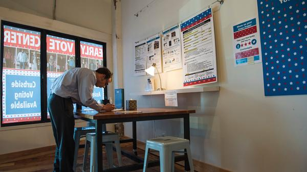 A man registers to vote at the Early Vote Center in Minneapolis on Oct. 5.