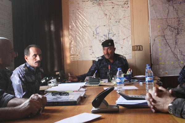 Police Gen. Abdulkareem al-Jubouri (center) meets with other police officers outside of Mosul. The police are eager to reclaim their home city from the Islamic State, but some policemen speak openly of seeking revenge.
