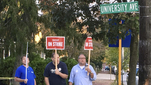 Picketers hold signs near Pennsylvania's West Chester University on Wednesday. Professors at state universities, including West Chester, came to a tentative contract agreement with the state on Friday.