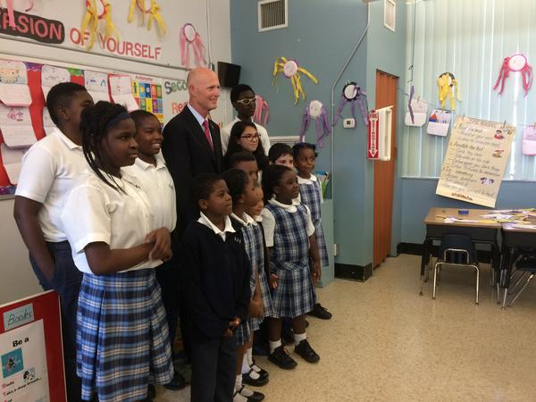 Florida Gov. Rick Scott poses with students at St. Mary Cathedral School in Miami's Little River neighborhood, prior to a Zika roundtable with local officials.