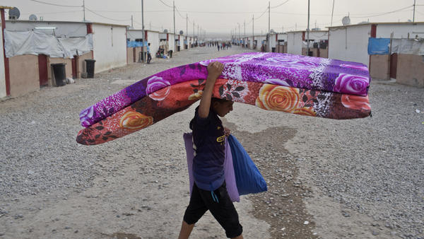 A boy carries mattresses at a camp for displaced families in Debaga, about 50 miles southeast of Mosul, Iraq, on Monday. Camp residents who recently fled areas controlled by the Islamic State say they expect the extremist group to put up a tough fight in Mosul and surrounding areas.