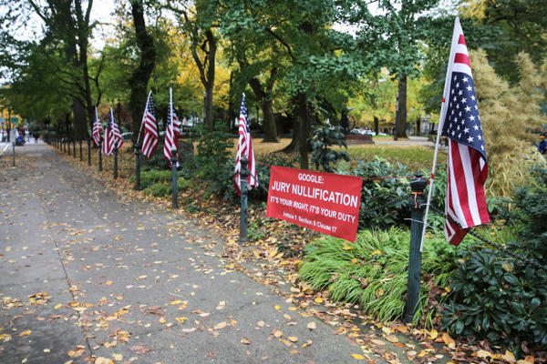 <p>Outside the courthouse stood a half-dozen American flags and a red sign that instructed the jury to ignore the law if they disagree with it &mdash; a message encouraging jury nullification.</p>