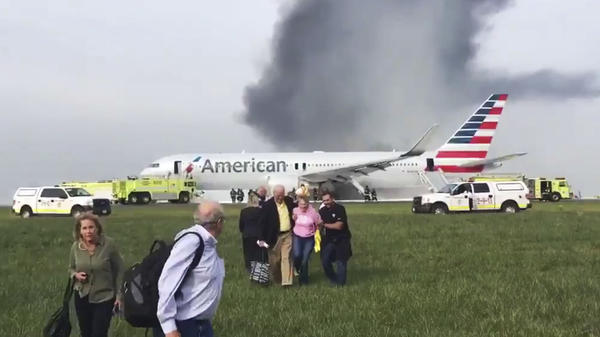 Passengers walk away from an American Airlines jet that aborted a takeoff and caught fire at Chicago's O'Hare International Airport. No serious injuries were reported.