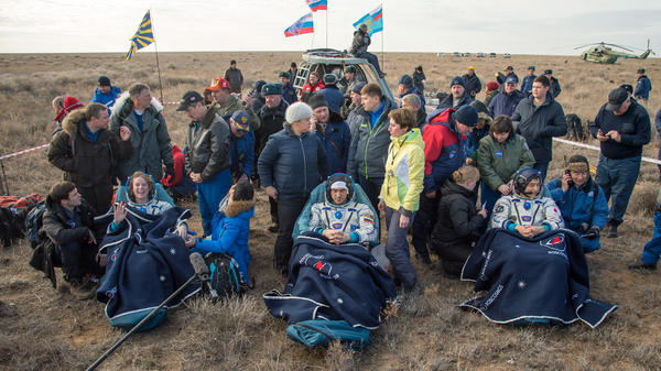 NASA astronaut Kate Rubins, left, Russian cosmonaut Anatoly Ivanishin of Roscosmos, center, and astronaut Takuya Onishi of the Japan Aerospace Exploration Agency sit outside the Soyuz MS-01 spacecraft a few minutes after they touched down on earth Sunday.