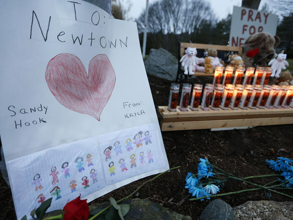 A child's message rests with a memorial for shooting victims on Sunday in Newtown, Conn.