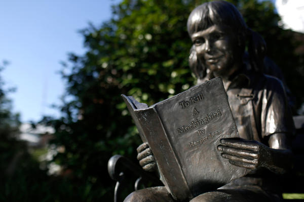 A statue of a young girl reading <em>To Kill a Mockingbird</em> in Lee's hometown of Monroeville, Ala.