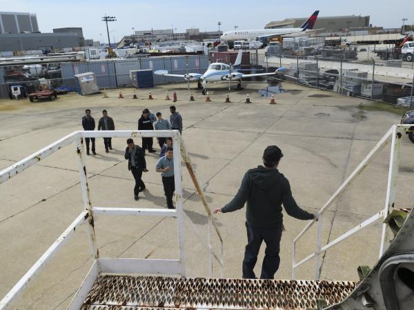 Mike Fisher, a teacher at Aviation High School, talks to students from the stairs leading up to the school's Boeing 727.