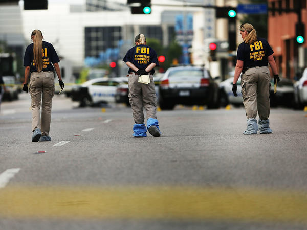 Members of an FBI evidence response team search an area in downtown Dallas following the deaths of five police officers on Thursday night.