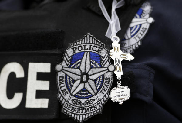 Dallas police officer Kimberly Howard wears a cross given to her earlier in the day by a random well-wisher outside department headquarters in Dallas on Saturday.