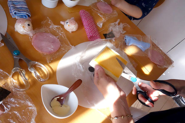 At a class outside Tokyo, Japanese moms learn how to fashion a ham and cheese sandwich into small flower.