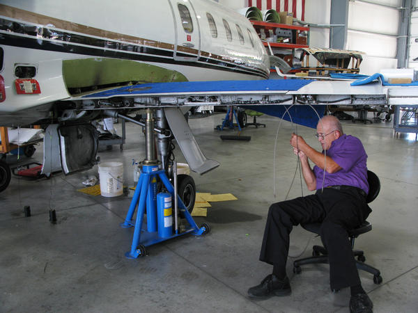 Mike Catherwood works on a Lear jet in a hangar in Springfield. The retired Air Force mechanic says his company, Spectra Jet, has so much work it needs more space.