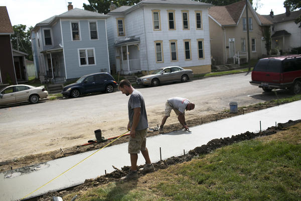 People work on restoring a sidewalk in Springfield. The loss of so many jobs has caused the city's population to drop from more than 80,000 in the 1970s to fewer than 60,000 today.