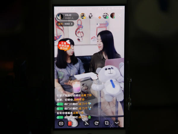 Huang Xian'er (right) is seen on a smartphone, live-streaming a chat with a guest. As they talk, little emoticons — hearts, flowers, gifts — waft across the screen.