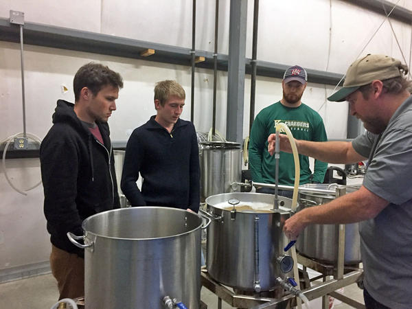 Program Director Steve Wagner, right, helps students during a lab class at CWU in Ellensburg, Washington. They are making wort. It's one of the first steps in the beer making process, during which sugars are extracted from milled grain.