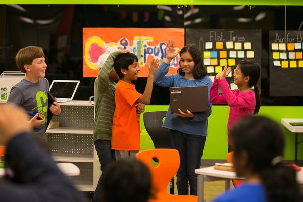Students high-five and share a laugh at the Khan Lab School.