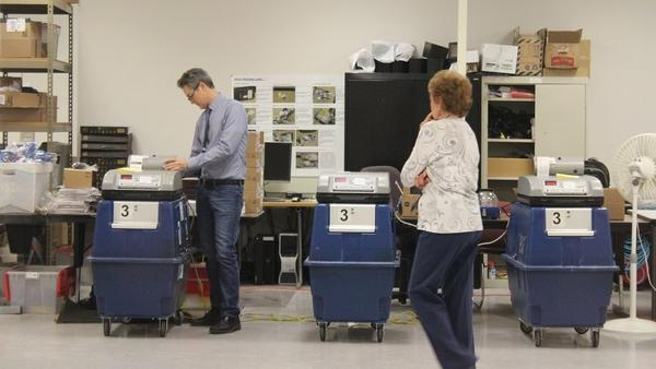 Election officials test ballot tabulation machines in Phoenix.
