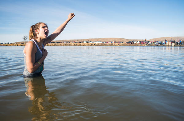 Stephanie Jasper holds up her fist and yells while protesting in the Cannonball River during a standoff with police at Turtle Island, north of the Standing Rock Sioux Reservation.